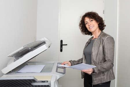 fotocopiadora: Vista lateral de un empleado de oficina mujer usando una fotocopiadora en la oficina Foto de archivo
