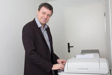 copy machine: Joyful business man smiling near a copy machine at work