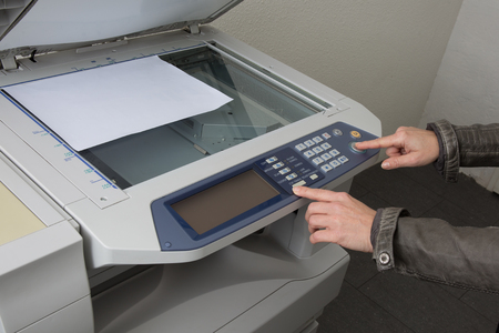 copy machine: Office life, hand pressing start button on a copy machine