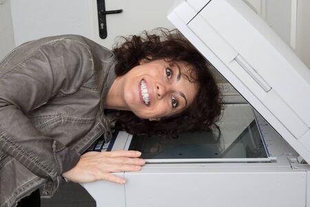 fotocopiadora: chica bonita que controla la máquina fotocopiadora escáner poniendo su cabeza en el interior