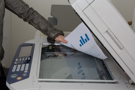 copy machine: Woman scan some documents at work on a copy machine
