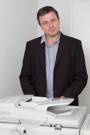 copy machine: Handsome smiling confident businessman portrait at copy machine
