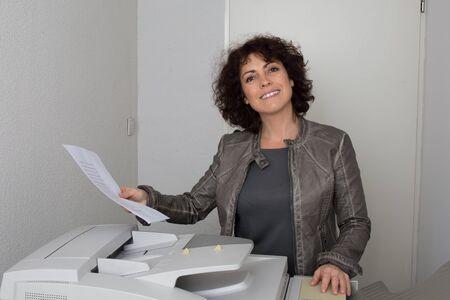 copy machine: Happy businesswoman holding a paper close to copy machine Stock Photo
