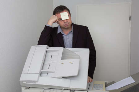 out of order: man in office near copier with a paper out of order on his face Stock Photo