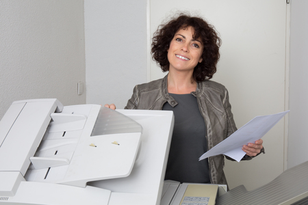 copy machine: Happy and smiling secretary using a copy machine at work Stock Photo