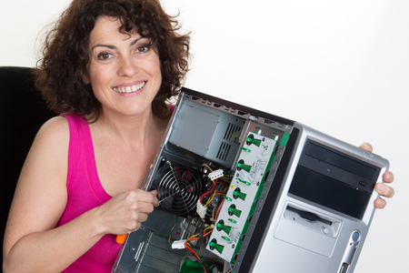 computer parts: Girl repairing the system unit at business place Stock Photo