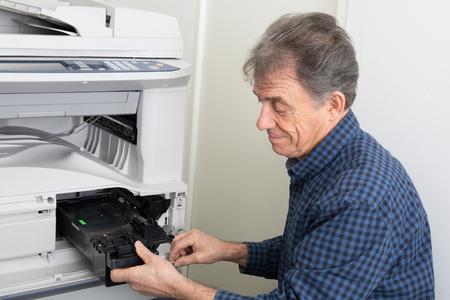 photocopier: Shot of senior male technician holding toner cartridge in digital photocopier machine Stock Photo