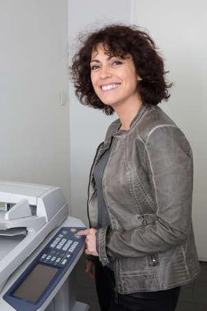 fotocopiadora: Vista lateral de una mujer de pie delante de una fotocopiadora
