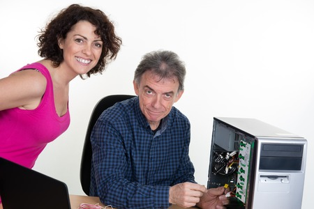 microcomputer: Man is fixing computer with woman watching it Stock Photo