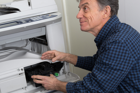 photocopy: Side view of businessman fixing cartridge in photocopy machine at office Stock Photo
