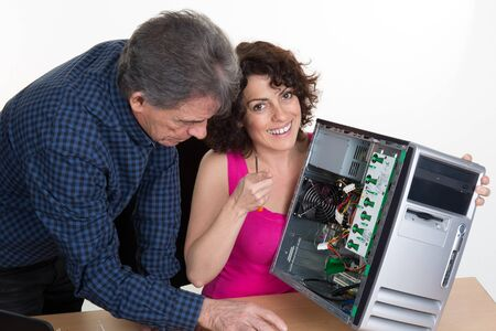 verifying: Portrait of a woman fixing a computer with a boss looking at her