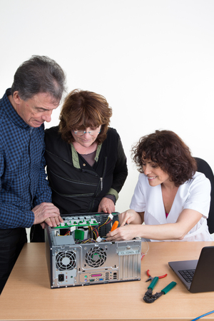 hardware repair: Technician repairing a computer and a senior couple is waiting for