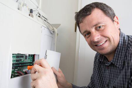 fotocopiadora: Shot handsome technician fixing a photocopier machine Foto de archivo