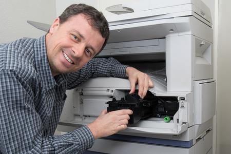 Homme technicien ouverture photocopieuse dans un bureau Banque d'images - 51444296
