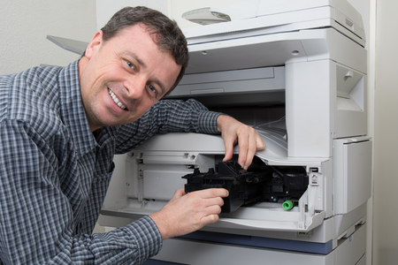Technician man opening photocopy machine in a office