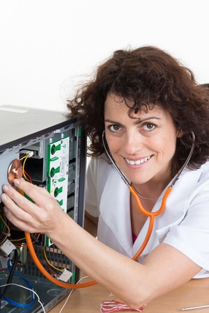 computer equipment: Female  with Stethoscope on computer - woman is fixing computer at office
