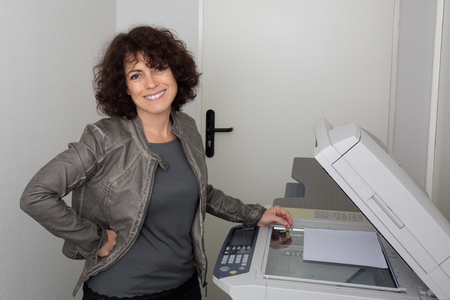 copy machine: Attractive woman working on copy machine in office Stock Photo
