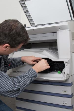 fotocopiadora: closeup shot male technician repairing digital photocopier machine