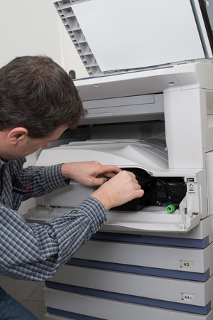 fotocopiadora: t�cnico de tiro masculino de cerca la reparaci�n de la m�quina copiadora digital