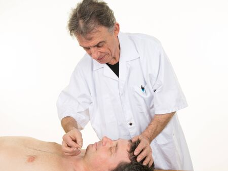chiropractic: Acupuncture needle of male patient by the reflexologist