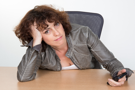 self assured: Bored businesswoman sitting at her desk in her office Stock Photo