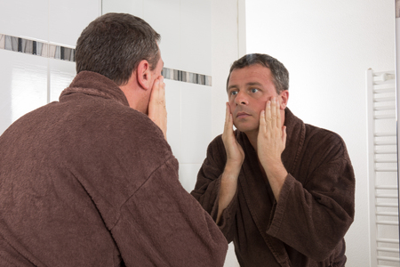 Skin care. Man applying cream at his face and looking at himself  while standing in front of the mirror Stock Photo