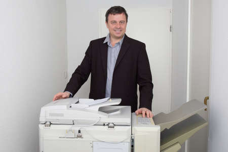 copying: Happy man is doing documents copies on copying machine in his office