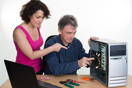 acknowledged: Man wearing a shirt is plugging cables of a computer, a woman is watching him