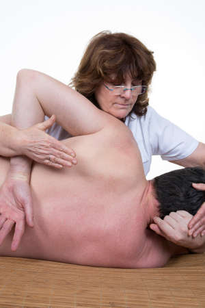 osteopath: Close up of osteopath doing spinal column rehabilitation exercise on young woman.