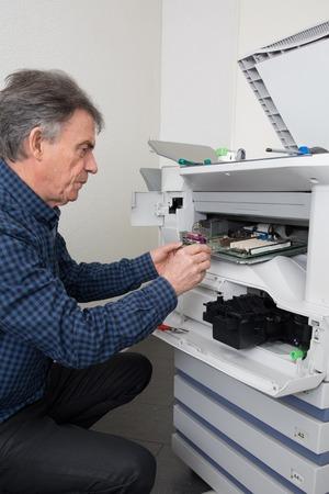 photocopier: closeup shotmale technician repairing digital photocopier machine