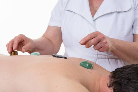 color therapist: therapist is placing healing stones on back of Caucasian middle-aged man