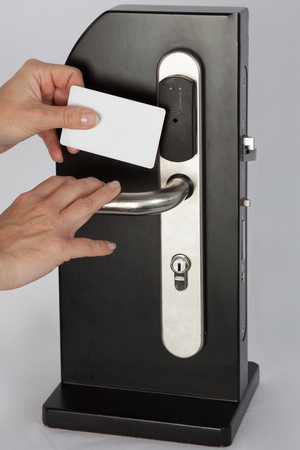 electronic pad: right hand hold key card touch on black electronic pad lock access control with stainless steel door handle Stock Photo