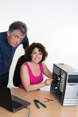 hardware repair: Man looking for woman trainee fixing computer at work Stock Photo