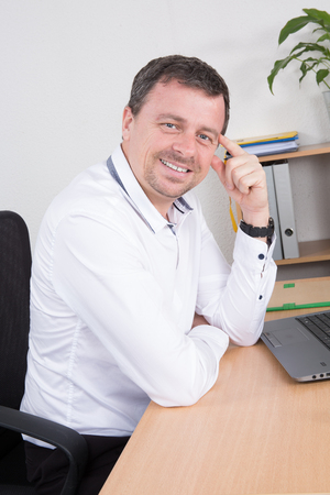 25 30 years: Cheerful guy sitting in front of desktop computer