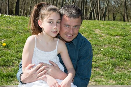 Girl is hugging her father - outside at the park