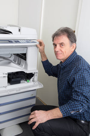 photocopier: Shot male technician repairing digital photocopier machine