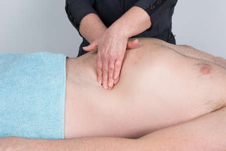 alternative practitioner: Macro close up of osteopaths hands doing manipulative visceral massage on man thorax.