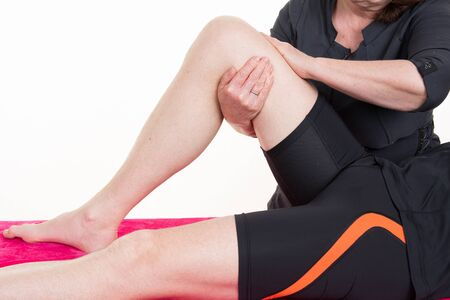 estiramiento: Una imagen de un masaje fisio terapeuta que da la rodilla sobre el fondo blanco