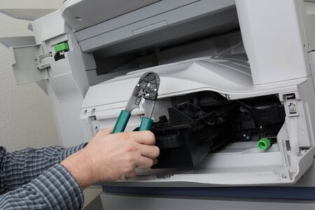 photocopy: Frustrated business man opening photocopy machine in office trying to fix problem Stock Photo