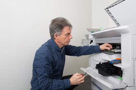 photocopier: Technician fixing broken photocopier machine at work