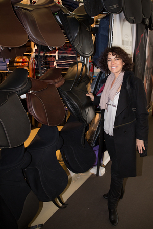 equine: Woman  contemplating horse saddle in the store at marketplace