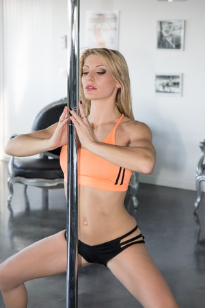arching: Young blond woman stretching and warming up for her pole fitness class