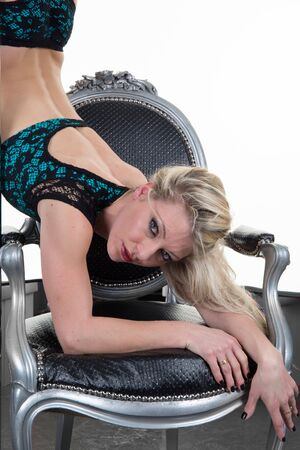 striptease women: Young sexy blond pole dance woman with a chair isolated