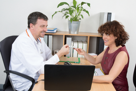 general practice: American doctor talking to woman in a surgery at a office Stock Photo