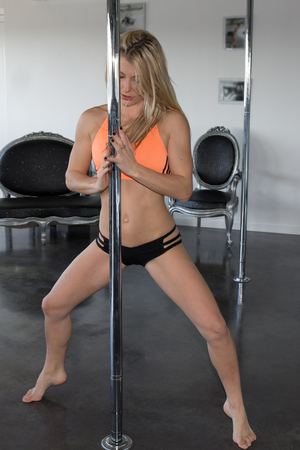 pole dancing: Sexy young brunette practicing some moves in a pole dancing class at a gym Stock Photo
