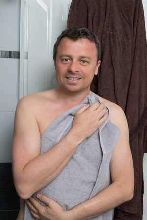 after bath: happy man applying after shower  Portrait of a  man with grey towel after bath