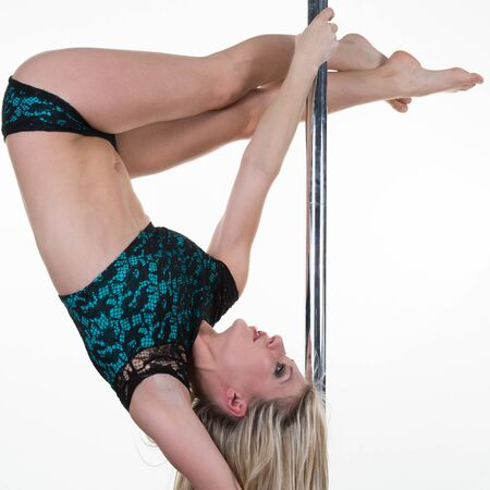 striptease: Young sexy woman exercise pole dance against a white background