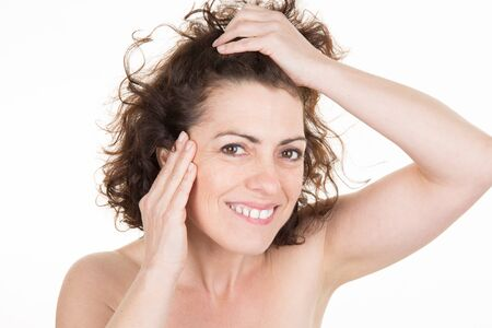 aghast: Woman staring at the first grey hair on her scalp, a first sign of aging, or noticing that she is suffering from dandruff
