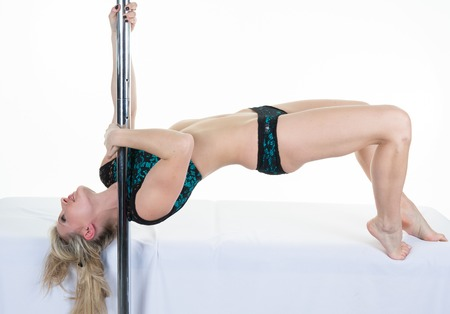 striptease women: Young sexy woman exercise pole dance against a white background