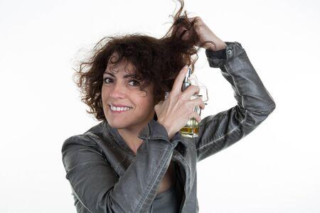 hair curly: La muchacha se aplica aceite en los extremos de su pelo rizado. De cerca.